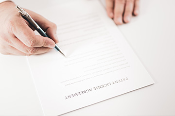 Attorney signing a patent license agreement